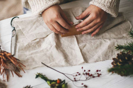 Female hands in cozy sweater wrapping christmas gift in linen fabric on wooden table with green branch, pine cones, scissors. Plastic free christmas present, zero waste  holidays.