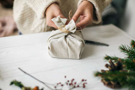 Woman in cozy sweater preparing plastic free christmas present. Female hands wrapping stylish christmas gift in linen fabric on white rustic table with green branch, pine cones, scissors and twine. Standard-Bild