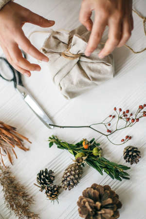 Hands wrapping stylish christmas gift in linen fabric on white rustic table with fir, pine cones, scissors, twine. Female preparing plastic free christmas present, zero waste holidays.