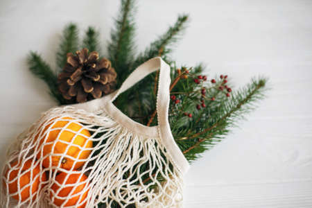 Net cotton bag with green spruce branches, oranges and pine cones on white rustic background. Reusable shopping bag with winter decorations, plastic free holidays. Top view