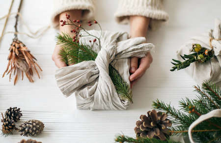Zero waste Christmas holidays. Hands holding stylish gift wrapped in linen fabric with green fir branch and red berries on rustic white table with pine cones. Plastic free holidays