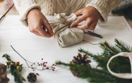 Female hands wrapping stylish christmas gift in linen fabric on white rustic table with green branch, pine cones, scissors and twine. Woman in cozy sweater preparing plastic free christmas present Standard-Bild