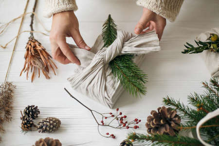 Florist preparing zero waste Christmas gift. Plastic free holidays. Hands decorating stylish christmas gift in linen fabric with green fir branch on white rustic table with pine cones and berries. Standard-Bild