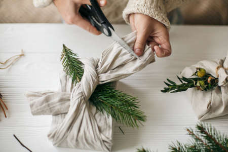 Hands wrapping gift in linen fabric with natural green branch on background of white rustic table. Florist preparing present, holding scissors. Zero waste stylish christmas gift. Standard-Bild