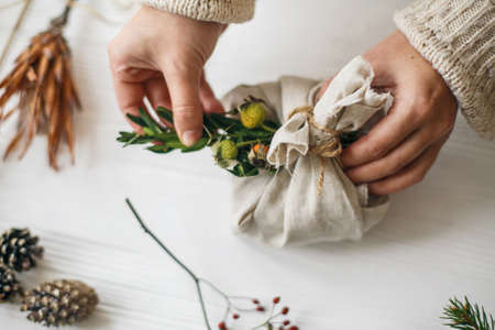 Hands decorating stylish christmas gift in linen fabric with green branch on white rustic table with natural herbs and pine cones. Female preparing plastic free christmas present. Standard-Bild