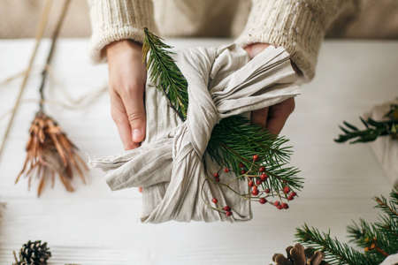 Zero waste Christmas holidays. Hands holding stylish gift wrapped in linen fabric with green fir branch and red berries on rustic background. Plastic free sustainable lifestyle