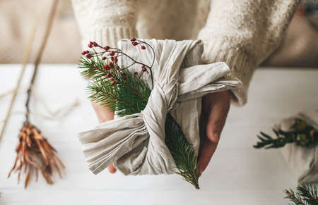 Zero waste Christmas gift. Hands holding stylish gift wrapped in linen fabric with green fir branch and red berries on rustic background. Plastic free sustainable lifestyle Standard-Bild
