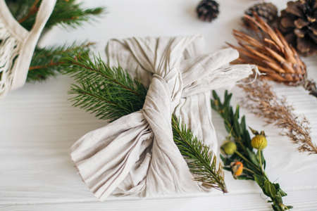 Stylish christmas gift flat lay. Present wrapped in linen fabric decorated with natural fir branch on white rustic table background with pine cones and herbs. Zero waste winter holidays