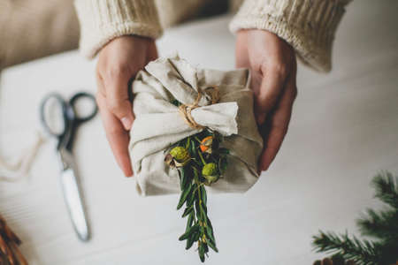 Zero waste Christmas gift. Hands holding stylish present wrapped in linen fabric with natural green branch on rustic background  with pine cones and scissors. Plastic free holidays Standard-Bild