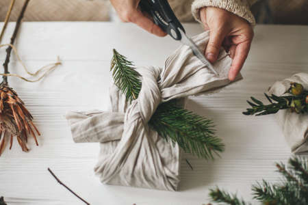 Zero waste stylish christmas gift. Hands wrapping gift in linen fabric with natural green branch on background of white rustic table. Florist preparing present, holding scissors