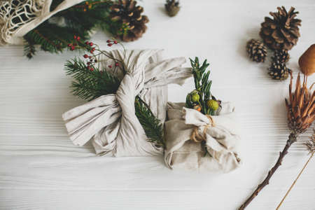 Stylish christmas gifts wrapped in linen fabric, decorated with natural green branch on white rustic table background with pine cones and herbs. Zero waste winter holidays.