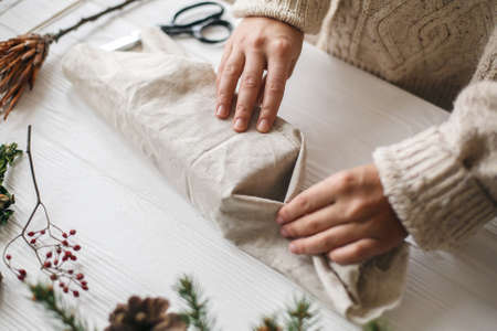 Plastic free christmas present, zero waste  holidays. Female hands in cozy sweater wrapping christmas gift in linen fabric on wooden table with green branch, pine cones, scissors. Standard-Bild