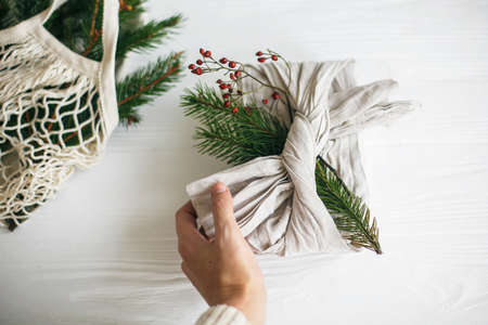 Hand holding stylish christmas gift wrapped in linen fabric with green fir branch on rustic white wooden background. Zero waste christmas holidays. Sustainable lifestyle