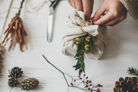 Female preparing zero waste christmas present. Hands decorating stylish christmas gift in linen fabric with green branch on white rustic table with natural herbs and pine cones. Standard-Bild