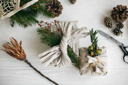 Zero waste stylish christmas gift. Gift wrapped in linen fabric with natural green branch on white rustic table background with fir and scissors. Plastic free holidays.