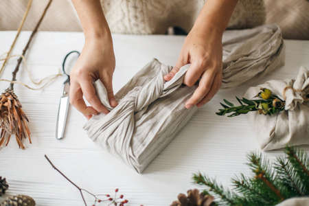 Hands wrapping christmas gift in linen fabric in furoshiki style on white rustic table with natural fir, herb, pine cones and scissors. Female preparing plastic free christmas present