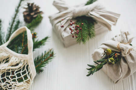 Stylish christmas gifts wrapped in linen fabric with green branch and reusable shopping bag with green spruce on rustic wooden background. Zero waste christmas holidays. Sustainable lifestyle