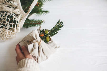 Zero waste christmas holidays. Hand holding stylish christmas gift wrapped in linen fabric with green  branch on rustic white wooden background.  Sustainable lifestyle