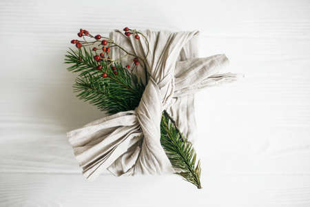 Stylish christmas gift, flat lay. Present wrapped in linen fabric and decorated with natural fir branch and red berries on white rustic table background. Zero waste winter holidays.