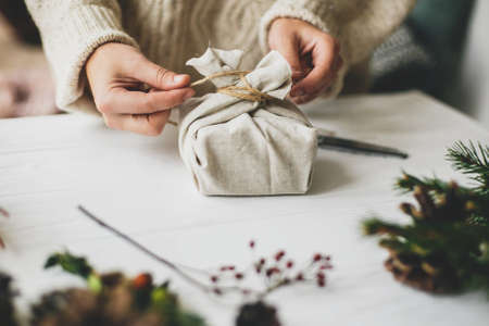 Female in cozy sweater preparing plastic free christmas present, zero waste. Hands wrapping stylish christmas gift in linen fabric on white rustic table with fir, pine cones, scissors, twine.