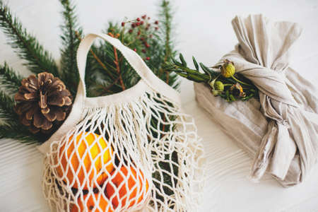 Stylish christmas gift wrapped in linen fabric with green branch and reusable shopping bag with green spruce and oranges on rustic wooden background. Zero waste christmas holidays Standard-Bild