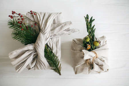 Stylish christmas gifts wrapped in linen fabric and decorated with natural green branches on white rustic table background, flat lay. Zero waste christmas holidays. Standard-Bild