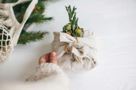 Hand holding stylish christmas gift wrapped in linen fabric with green  branch on rustic white wooden background. Zero waste christmas holidays. Sustainable lifestyle