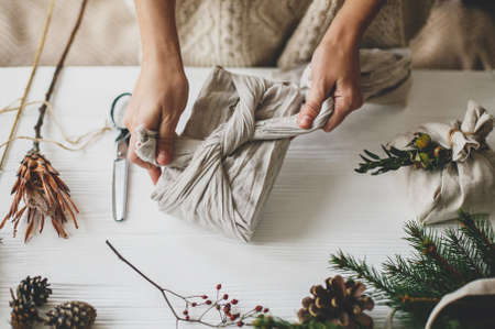 Plastic free holidays, zero waste Christmas. Hands wrapping christmas gift in linen fabric in furoshiki style on white rustic table with natural fir, herb, pine cones and scissors.