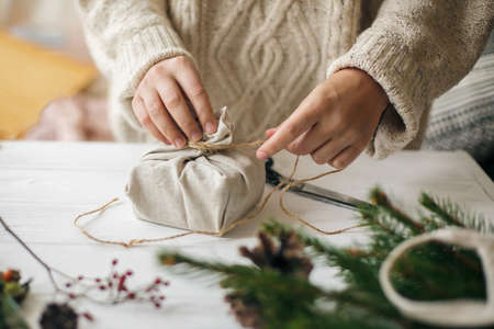 Hands wrapping stylish christmas gift in linen fabric on white rustic table with fir, pine cones, scissors, twine. Female in cozy sweater preparing plastic free christmas present, zero waste Standard-Bild