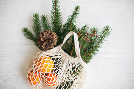 Reusable cotton bag with green spruce branches, oranges and pine cones on white rustic background. Net shopping bag with winter decorations, zero waste holidays. Top view