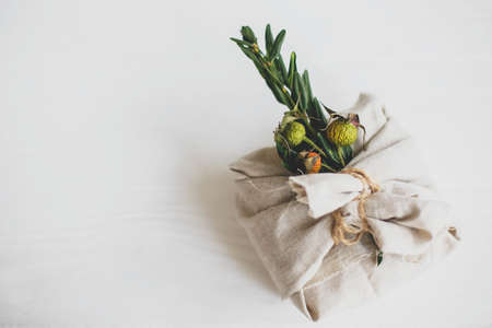 Zero waste christmas holidays. Stylish christmas gift wrapped in linen fabric and decorated with natural green branch on white rustic table background, space for text.