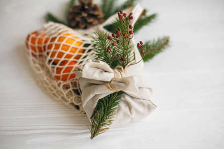 Stylish christmas gift wrapped in linen fabric with natural green branch and red berries on background of reusable cotton bag with oranges on white  table. Zero waste christmas holidays