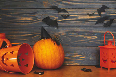 Pumpkin with spider and witch hat, Jack o lantern candy bucket and bats on dark background. Handmade holiday decorations, celebrating halloween at home. Happy Halloween! Imagens