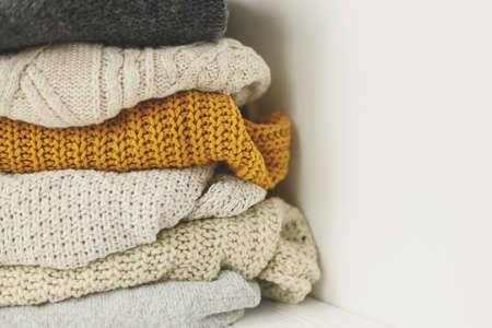 Cozy knitted sweater stack for cold autumn weather on white background. Stylish white, yellow and grey sweaters close up with space for text. Hello fall! Standard-Bild