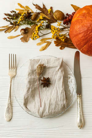 Stylish and zero waste Thanksgiving table setting. Plate with cutlery, linen napkin, anise and autumn leaves, pumpkin, autumnal flowers on white table. Rustic autumn wedding table set.