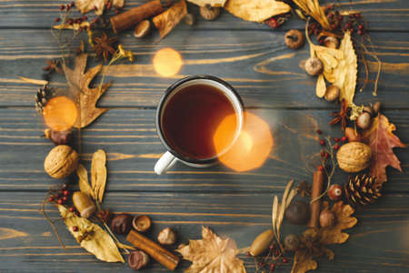 Hello fall! Cozy autumn flat lay. Rustic metal mug with tea and autumn wreath made of leaves, berries, acorns and pine cones on dark wooden background.