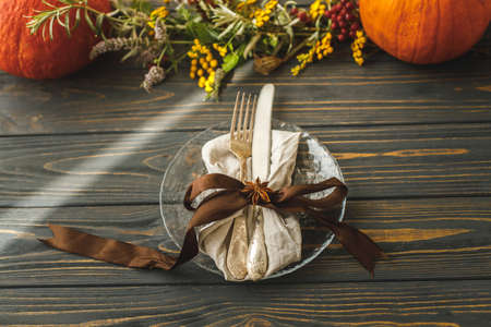 Zero waste Thanksgiving dinner. Stylish plate with cutlery and autumn decorations, pumpkin, natural branches and autumnal flowers on rustic table. Autumn wedding Standard-Bild