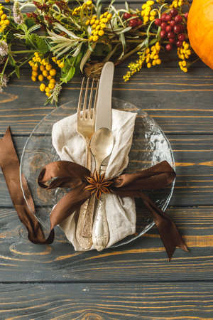 Eco friendly Thanksgiving dinner. Stylish plate with cutlery and autumn decorations, pumpkin, natural branches and autumnal flowers on rustic table. Autumn wedding table setting