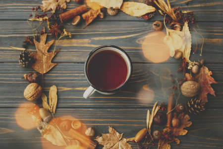 Hello fall! Rustic autumn flat lay. Vintage metal mug with tea and autumn wreath made of leaves, berries, acorns and pine cones on dark wooden background with warm lights.