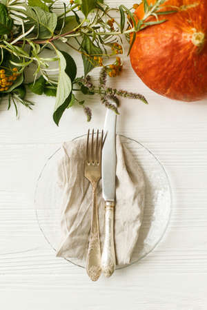 Thanksgiving dinner table setting, eco friendly arrangement. Stylish plate with cutlery and autumn decorations, pumpkin, natural branches and autumnal flowers on white table.