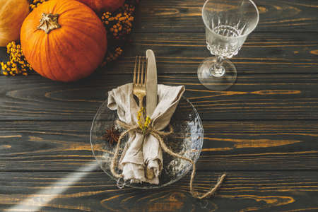 Thanksgiving dinner table setting. Stylish plate with cutlery, linen napkin and pumpkin with autumnal flowers on rustic table. Autumn wedding catering, eco friendly arrangement Standard-Bild