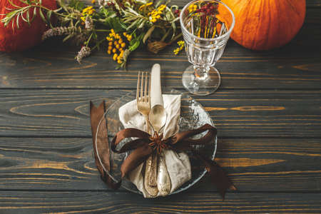 Thanksgiving dinner table setting. Stylish plate with cutlery and autumn decorations, pumpkin, natural branches and autumnal flowers on rustic table. Autumn wedding catering Standard-Bild
