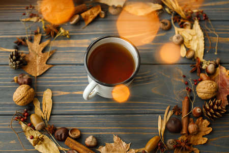 Vintage metal mug with tea and autumn wreath made of leaves, berries, acorns and pine cones on dark wooden background with warm lights. Hello fall! Rustic autumn image Standard-Bild