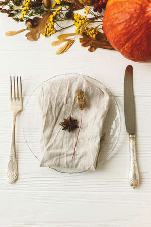 Eco friendly Thanksgiving feast. Stylish plate with cutlery, linen napkin, anise and autumn leaves, pumpkin,  autumnal flowers on white table. Rustic table setting decor