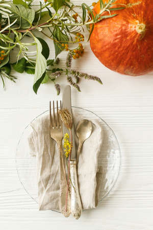 Eco friendly Thanksgiving feast. Stylish plate with cutlery and autumn decorations, pumpkin, natural branches and autumnal flowers on white table. Rustic table setting decor