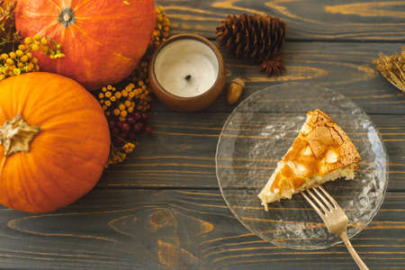 Apple pie slice on glass plate on rustic wooden table with candle, pumpkin, autumn flowers and pine cones. Homemade charlotte with apples, autumn cake simple recipe