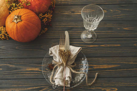 Eco friendly Thanksgiving dinner table setting. Stylish plate with cutlery, linen napkin with herb and pumpkin with autumn flowers on rustic table. Farmhouse rustic autumn wedding