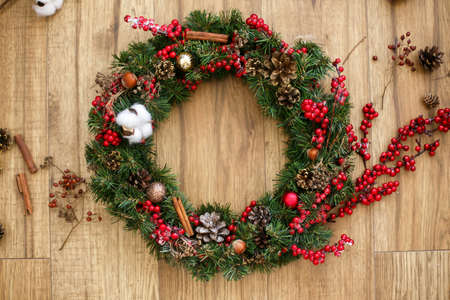 Christmas wreath on wooden rustic background flat lay. Traditional christmas wreath with red berries and ornaments, pine cones on wood. Holiday decorations for workshop. Space for text Archivio Fotografico