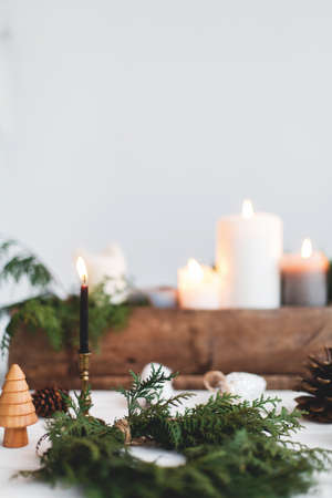 Making simple stylish christmas wreath with cedar branches, holiday workshop advent. Rustic christmas wreath with candles, pine cones, thread and ornaments on white wooden table.