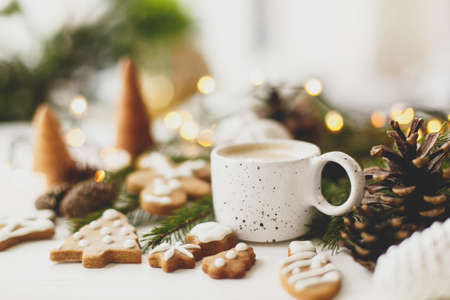 Christmas gingerbread cookies, coffee in stylish white cup, pine cones  and warm lights on white wooden table. Hello winter, cozy moody image with selective focus Stock Photo
